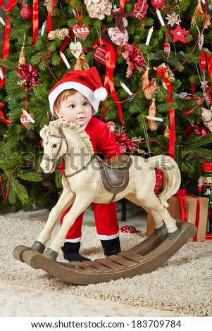 Little girl dressed in santa suit stands with rocking horse under Christmas tree on furry rug - stock photo