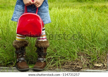 Little girl dressed in striped tights and a denim skirt is standing by a field and holding a red bag