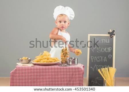 Little girl dressed in white chef hat and apron preparing pasta. Child blonde in the kitchen helps parents to prepare lunch. - stock photo