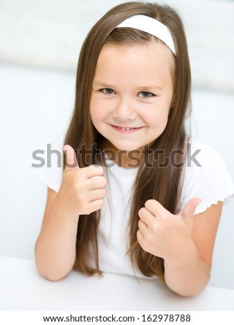 Little girl dressed in white is showing thumb up gesture using both hands - stock photo