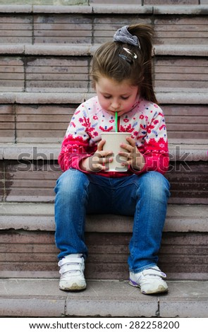 little girl drinking a milkshake through a straw while sitting on the stairs in the park - stock photo