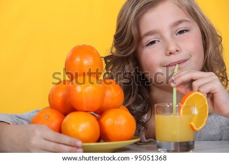 Little girl drinking freshly squeezed orange juice - stock photo