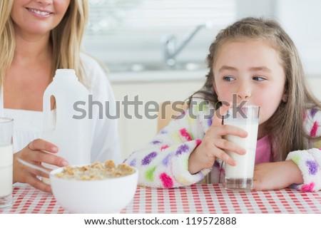 Little girl drinking milk at the kitchen - stock photo
