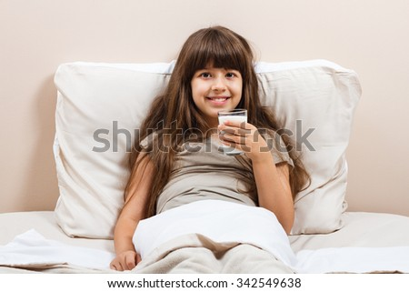 Little girl drinking milk in bed.Glass of milk for beautiful little girl - stock photo