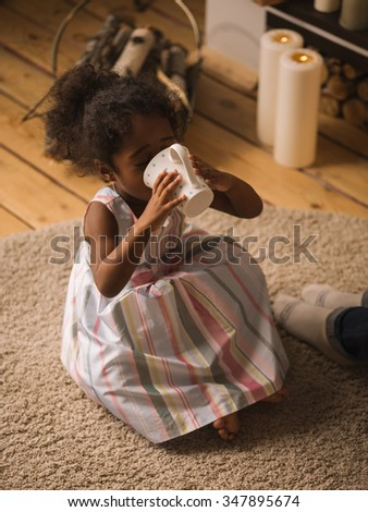Little Girl drinking milk or tea at home - stock photo