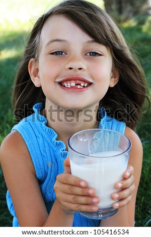Little girl drinking milk with a milk mustache. Shallow depth of field with selective focus on little girl's face. - stock photo