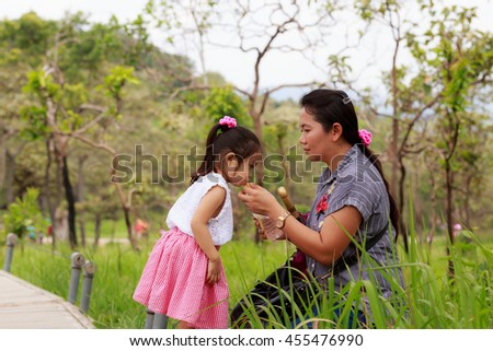 Little girl drinking water in bottles with young mother. - stock photo