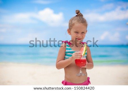 Little girl drinks juice from watermelon on the exotic beach