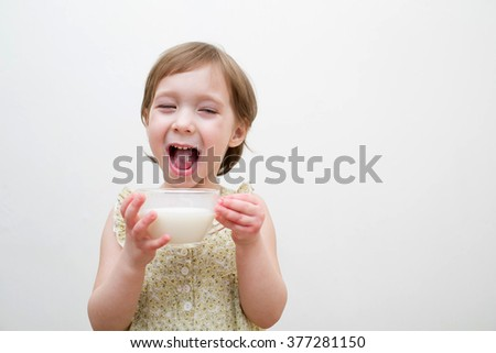 Little girl drinks milk , closed her eyes and opened her mouth with pleasure - stock photo