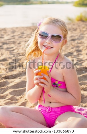 little girl drinks orange juice outdoor - stock photo