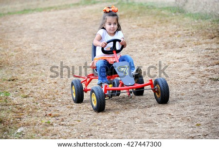 Little girl drives a go cart on a dirt track in Tennessee.  She has a determined look on her face as she gives it her all. - stock photo