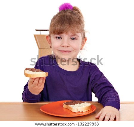 little girl eat bread with chocolate cream