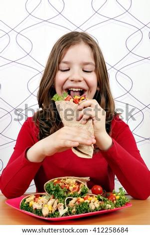 little girl eat burritos  - stock photo