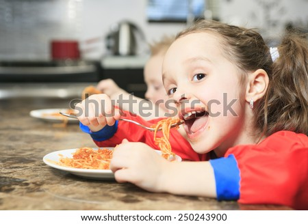 Little girl eat pasta in the kitchen table - stock photo