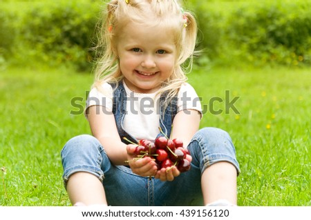 little girl eating a cherry in nature. in the park