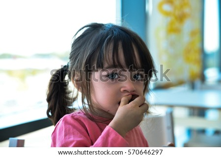 Little girl eating a chocolate cookie