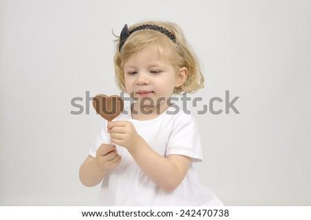 little girl eating a chocolate lollipop - stock photo