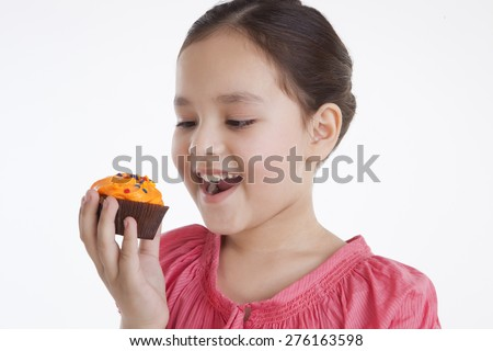Little girl eating a cupcake