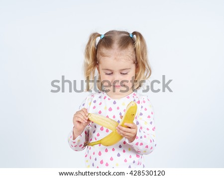 Little girl eating a fresh banana. Healthy eating. Diet. Vegetarianism. - stock photo