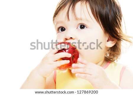Little girl eating a fresh red apple - stock photo