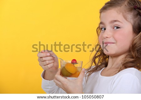little girl eating a fruit salad