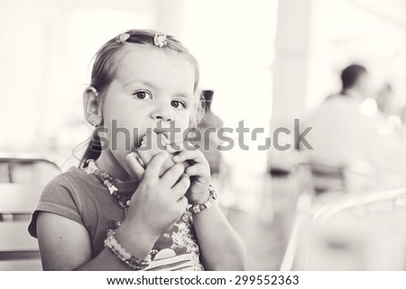 little girl eating a hamburger in outdoor cafe