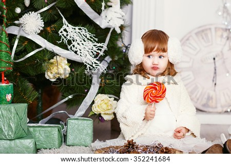 Little girl eating a lollipop. Portrait of a funny little baby girl in earmuffs with a delicious candy in the hands. Christmas and New Year concept