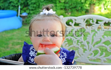 Little girl eating a piece of watermelon at a summer picnic