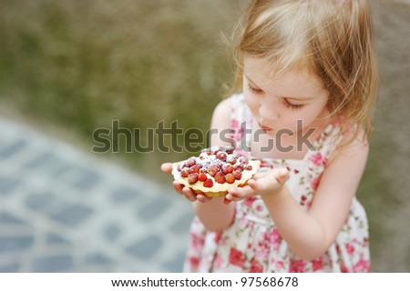 Little girl eating a strawberry tart outdoors - stock photo