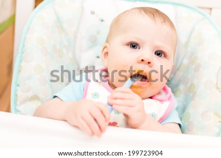 Little girl eating baby food in high chair.
