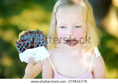Little girl eating belgian waffle on a stick outdoors on warm summer day - stock photo