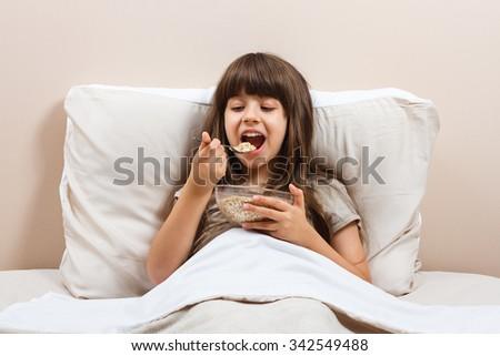 Little girl eating breakfast in bed.Healthy breakfast in bed - stock photo