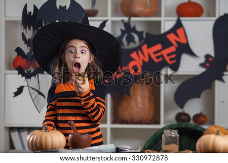 Little girl eating cookies at a halloween party - stock photo