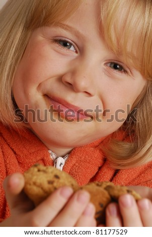 Little girl eating cookies,kid holding cookies. - stock photo