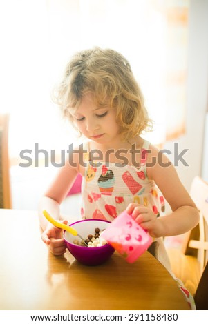 Little girl eating corn balls in the kitchen. Morning light - stock photo