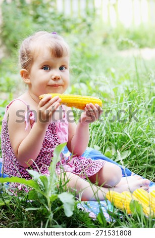 Little girl eating corn in the garden