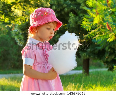 Little girl eating cotton candy in the park - stock photo