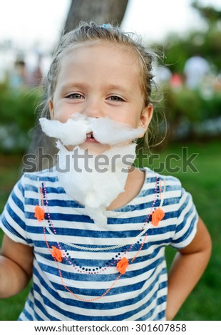 little girl eating cotton candy with mustache and beard - stock photo