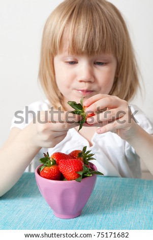 Little girl eating delicious ripe strawberries, bowl in front of her. - stock photo