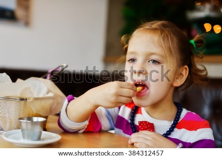 little girl eating french fries in a cafe