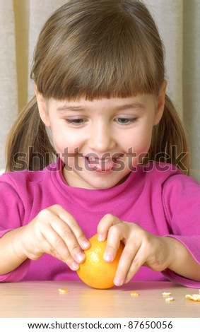 Little girl eating fresh tangerine. - stock photo