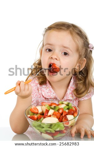Little girl eating fruit salad - healthy food concept - isolated - stock photo