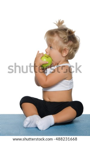 little girl eating green apple on white background