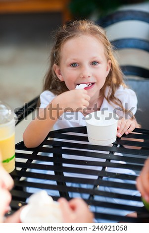 Little girl eating ice cream at outdoor cafe - stock photo