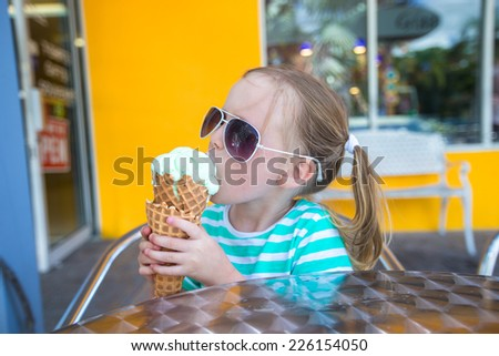 Little girl eating ice cream in a cafe outdoor - stock photo