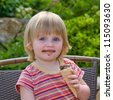 Little girl eating ice cream outdoor - stock photo