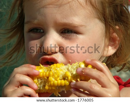 little girl eating messy corn on the cob - stock photo