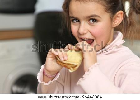 Little girl eating pancake - stock photo