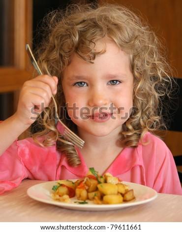 Little girl eating potatoes - stock photo