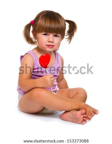 little girl eating red heart lollipop isolated on white - stock photo